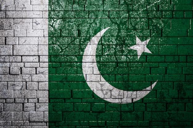 Bandiera nazionale del pakistan su sfondo di muro di mattoni.