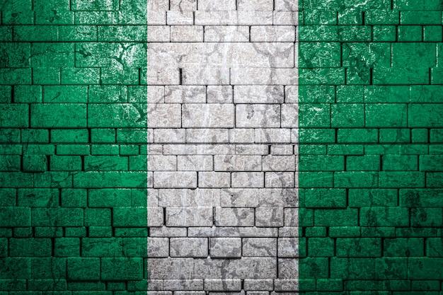 Bandiera nazionale della nigeria su sfondo di muro di mattoni.