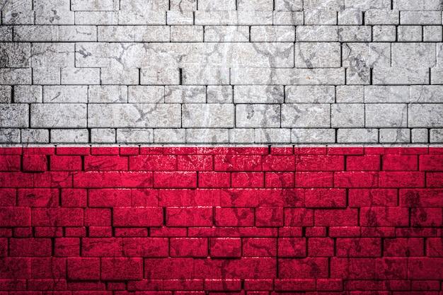 Bandiera nazionale della polonia su sfondo di muro di mattoni.