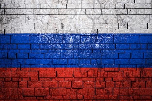 Bandiera nazionale della russia sul fondo del muro di mattoni.