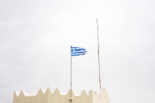 Bandiera nazionale greca sull'asta della bandiera che ondeggia contro il cielo blu, kos, grecia