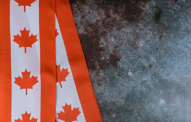 Bandiera rossa e bianca canadese contro fondo rustico scuro per la celebrazione del giorno del canada e le feste nazionali