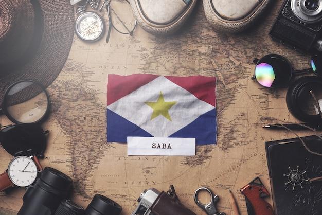 Bandiera saba tra gli accessori del viaggiatore sulla vecchia mappa vintage. colpo ambientale