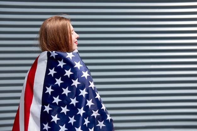 Bandiera stelle e strisce usa giovane donna rossa con labbra dipinte di rosso in piedi con bandiera usa sfondo grigio pannello metallico