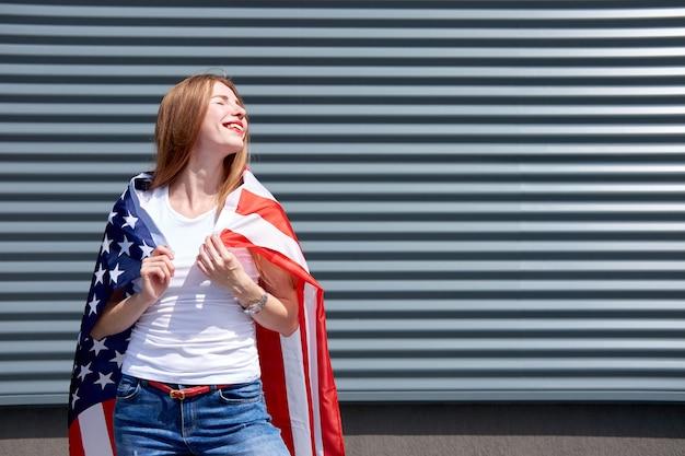 Bandiera usa a stelle e strisce. ragazza alla moda elegante dello zenzero con le labbra verniciate rosse e gli occhi chiusi che stanno con la bandiera di usa