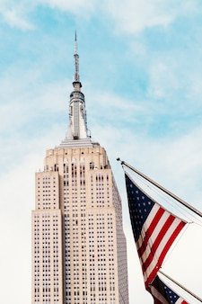 Bandiera usa che fluttua vicino all'empire state building