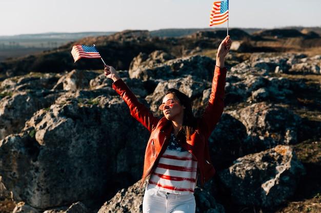 Bandiere americane d'ondeggiamento della bella donna su fondo roccioso