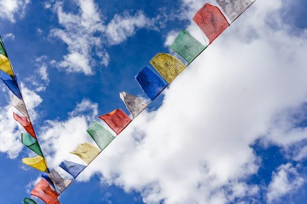 Bandiere buddisti variopinte di preghiera con uso vivo di colore come tailsman per il viaggio di sicurezza in tibetano sul fondo del cielo blu