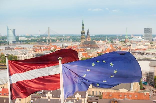 Bandiere della lettonia e dell'europena con paesaggio urbano di riga su fondo