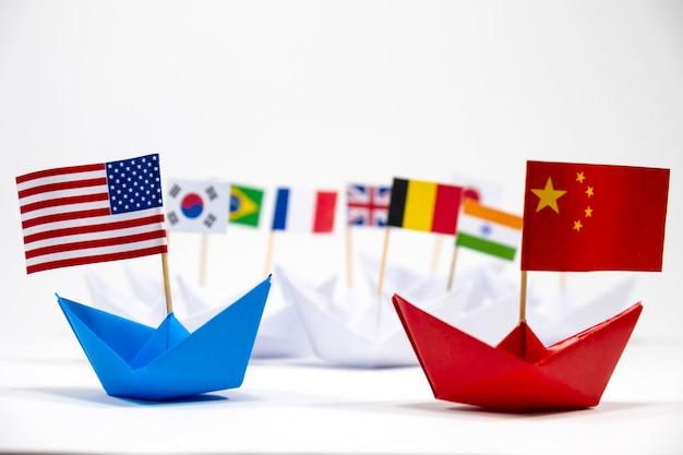 Bandierina degli stati uniti america sulla nave blu e sulla bandierina della cina sulla nave rossa con priorità bassa bianca del commercio di guerra