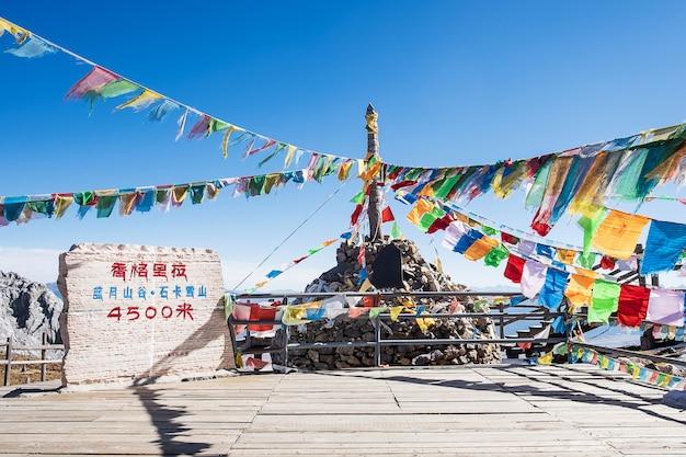 Bandierine di preghiera e stupa in vetta alla shika snow mountain o blue moon valley nella città di zhongdian