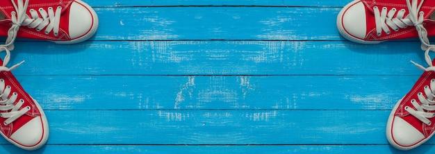 Banner con due paia di scarpe rosse per i giovani su una superficie di legno blu