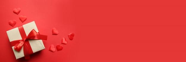 Banner creativo di san valentino. regalo di carta a sorpresa con nastri rossi e coriandoli a forma di cuore rosso su sfondo rosso. concetto di san valentino. vista piana, vista dall'alto, copia spazio