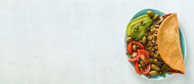Banner di colazione vegana di frittata di ceci senza uova senza glutine con funghi fritti e porro. e un'insalata di pomodori freschi maturi, avocado, olive e capperi.