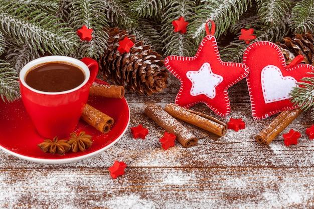 Banner di natale con albero verde, tazza con cioccolata calda, decorazioni fatte a mano in feltro, cannella.