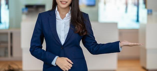 Banner e scena di copertura della reception asiatica che accoglie il cliente nel bancone dell'auto showroom per l'assistenza telefonica al cliente,
