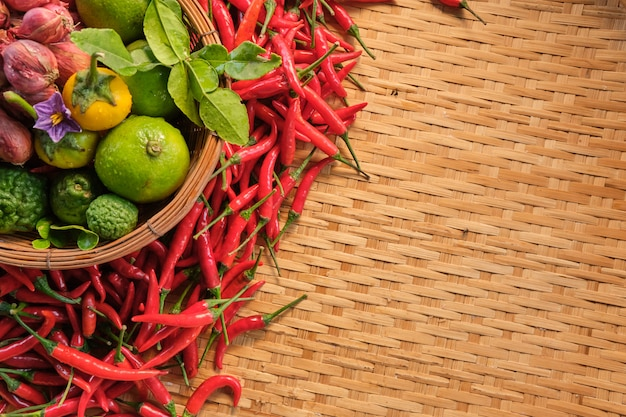 Banner isolato lato sinistro del tailandese tradizionale ingredienti alimentari nel cestino, peperoncini secchi, cipolle rosse, lime e verdura tailandese, layout posa sul modello di legno tradizionale tailandese rack in legno