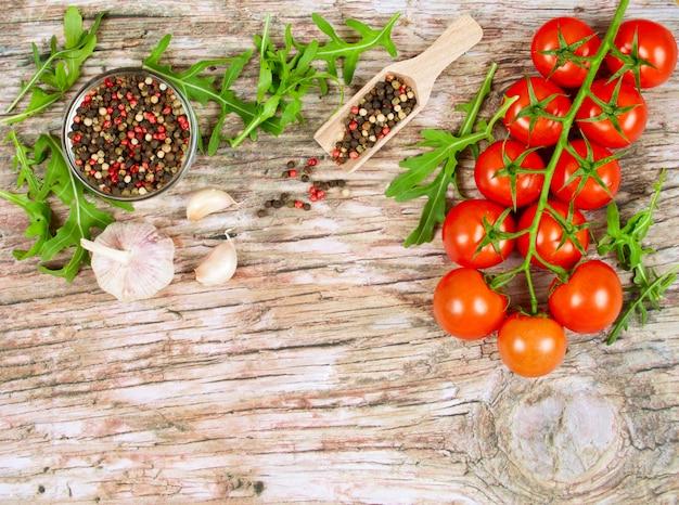 Banner orizzontale di cibo con pomodorini, rucola fresca, aglio e pepe in grani.
