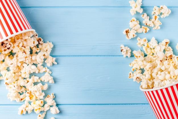 Banner orizzontale di popcorn. tazza e noccioli di carta spogliati rossi che si trovano sul fondo di legno blu.