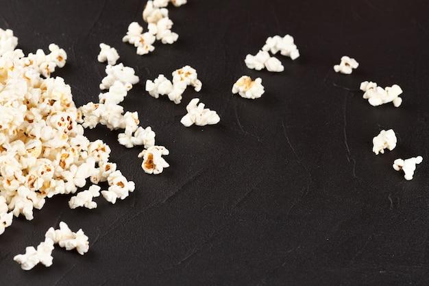 Banner orizzontale di popcorn. tazza e noccioli di carta spogliati rossi che si trovano sulla priorità bassa scura.