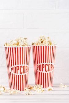 Banner verticale popcorn. tazza e noccioli di carta spogliati rossi che rimangono su fondo di legno bianco.