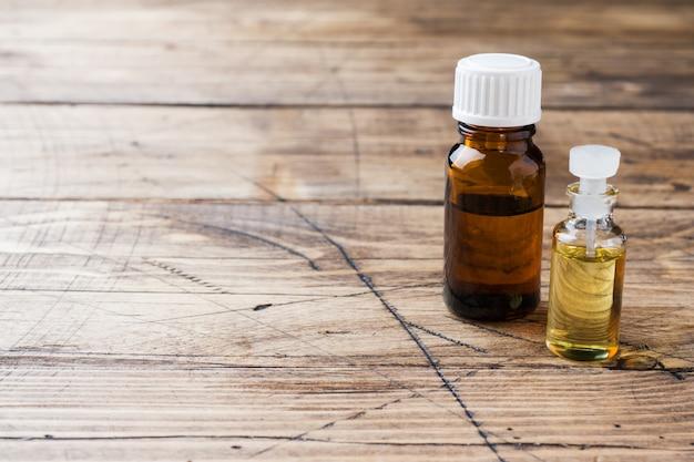 Barattoli di oli essenziali su uno sfondo in legno con spazio di copia.