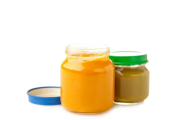 Barattoli di vetro con alimenti per bambini nutrienti isolati su superficie bianca