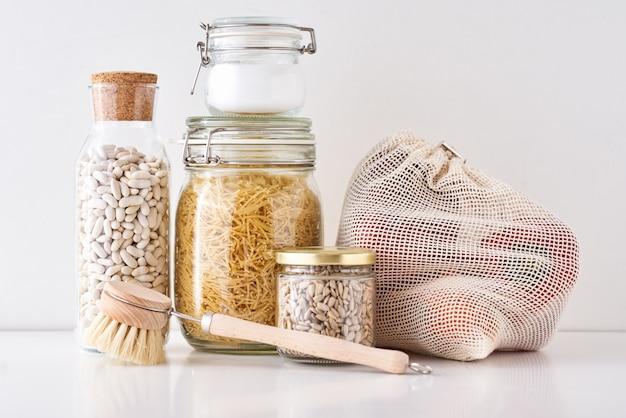 Barattoli di vetro con ingredienti alimentari su bianco, zero rifiuti concetto, cucina con utensili amichevoli eco