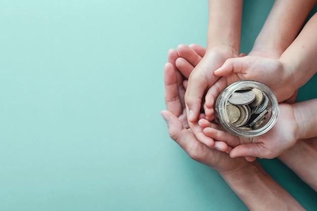 Barattolo dei soldi della tenuta dell'adulto e del bambino, donazione, concetto di risparmio