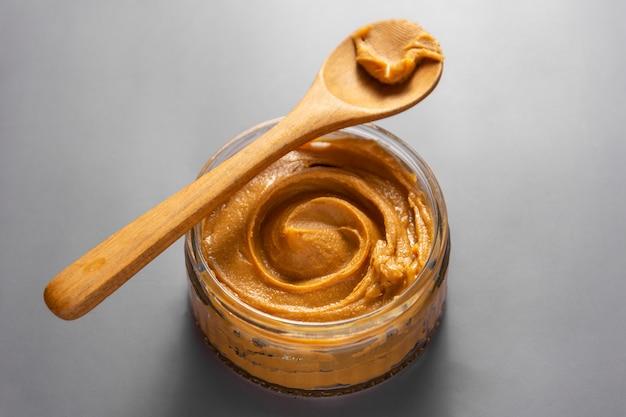 Barattolo di burro di arachidi con un cucchiaio di legno su sfondo grigio.