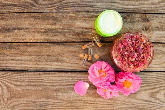 Barattolo di marmellata, crema per il viso, bottiglia di olio essenziale di petali di rosa su legno