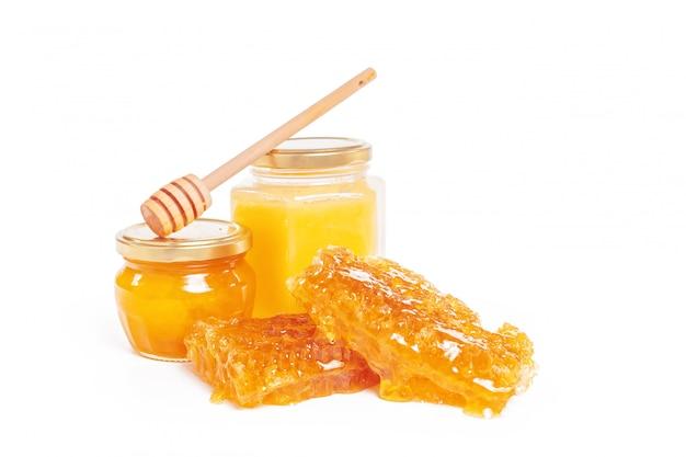Barattolo di miele e bastone isolato su bianco
