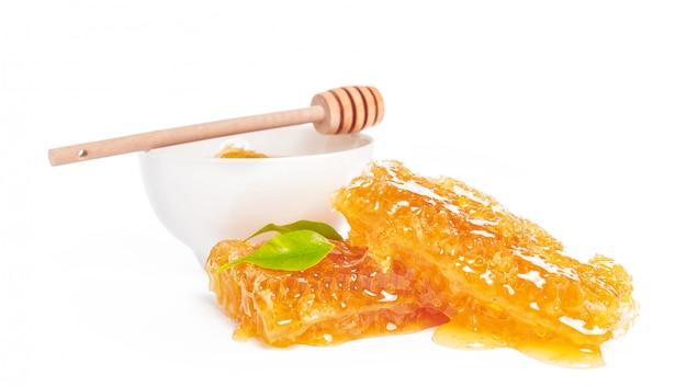 Barattolo di miele e bastone isolato