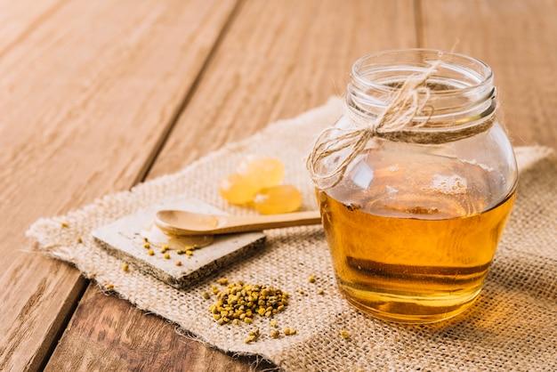 Barattolo di miele; semi di polline d'api e caramelle sul panno del sacco