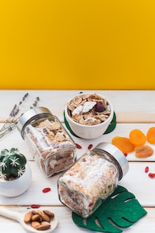 Barattolo di muesli e cornflakes vicino frutta secca; foglia finta e pianta grassa su superficie di legno