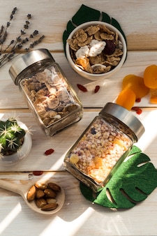 Barattolo di muesli; fiocchi di mais; frutta secca; foglia artificiale e pianta succulenta su superficie di legno