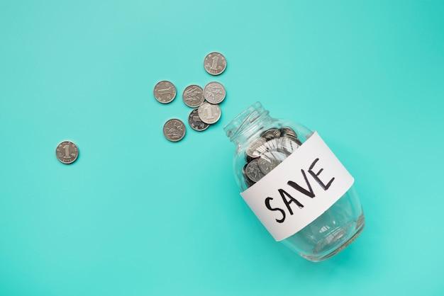 Barattolo di risparmio che si trova con le monete fuori