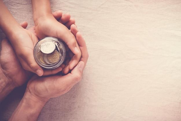 Barattolo di soldi della tenuta del bambino e dell'adulto, donazione, concetto di risparmio