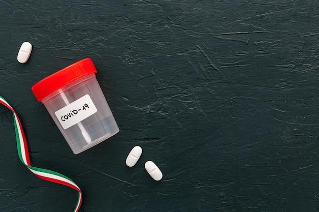 Barattolo di test covid-19 e pillole vicino a un nastro di bandiera italiana