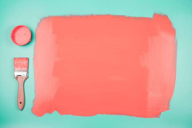 Barattolo di vernice corallina e pennello con sfondo verde acqua verniciata