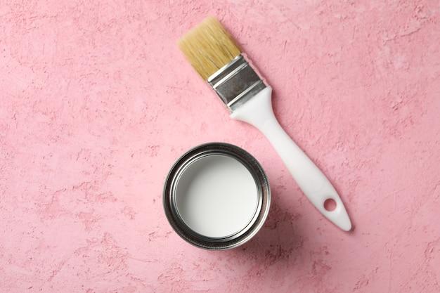 Barattolo di vernice e pennello sulla superficie rosa
