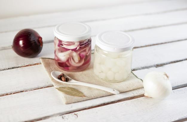 Barattolo di vetro delle cipolle marinate su fondo di legno bianco