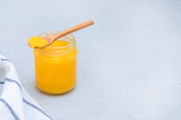 Barattolo di vetro di burro di ghi casalingo sano con il cucchiaio di legno sulla tavola di cemento