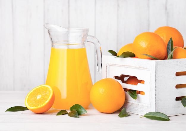 Barattolo di vetro di succo d'arancia fresco organico con le arance crude in scatola di legno bianca