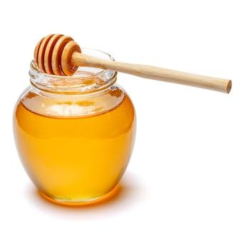 Barattolo di vetro pieno di miele e bastone di legno su uno spazio bianco. tracciato di ritaglio