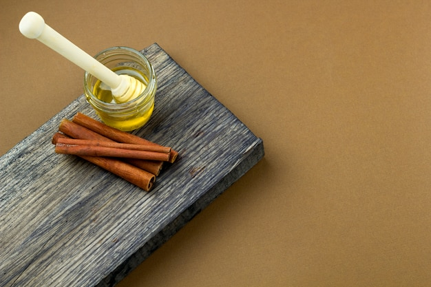 Barattolo e cannella del miele di vista superiore su uno spazio della copia del fondo di marrone di legno del bordo di legno