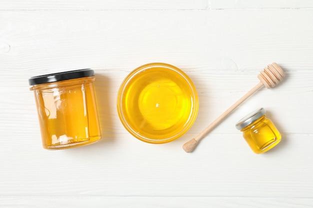Barattolo e ciotola di vetro con miele, merlo acquaiolo su fondo di legno bianco. disteso