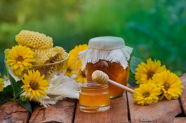 Barattolo e favo del miele sulla tavola di legno. barattolo e fiori del miele sulla tavola