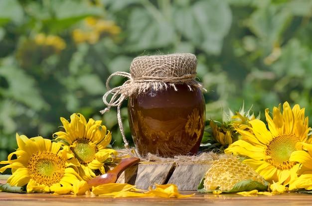 Barattolo e favo del miele sulla tavola di legno. vasetto di miele e fiori sul tavolo. copia spazio per il testo