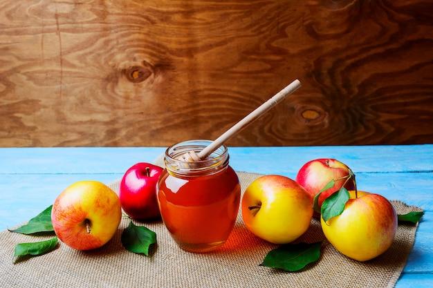 Barattolo e mele di vetro del miele sullo spazio rustico della copia del fondo